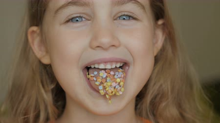 tongue out : Full of candy. Little girl eating candy. Child eating chicle. Close up portrait of silly girl with wavy hair sticking out tongue shaped candy pieces on tip.