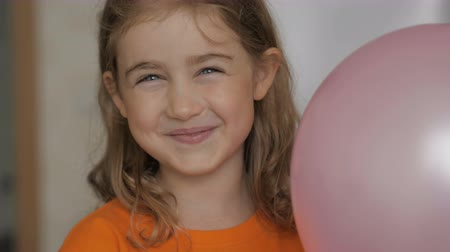 piada : Little girl looks happily from behind balloon and laughs happily. Close up portrait of a happy little child bursting in laugh. Child girl with blue eyes and laughs indoors. Closeup. Slow Motion.