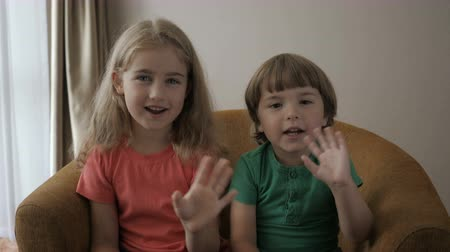 dizendo : Kids Girl And boy Making Online Video Call Recording Vlog Sitting Sofa, Portrait. Funny Friends Smiling Looking At Camera. Happy Little Children Saying Hello Hi Looking At Camera Talking To Webcam.