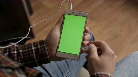telefonda : Male Using Touchscreen Mobile Phone. Young Man Home Sitting at Table with Green Screen Smartphone in Vertical Mode. Man Using Smartphone, Browsing Internet, Watching Video Content, Blogs. Pov. Stok Video