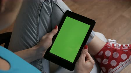 compresse : Girl Using Touchscreen Mobile Tablet. Young Woman Home Sitting on a Chair with Green Screen Tablet in Vertical Mode. Girl Using Smartphone, Browsing Internet, Watching Video Content, Blogs. Pov. Filmati Stock