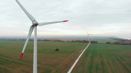 clean electricity production : Spinning Wind Turbines On Beautiful Sunset Autumn Landscape. Green Ecological Power Energy Generation. Wind Turbines Farm Eco Field. Sunrise Above Windmills On Field. Aerial View. Energy Production.