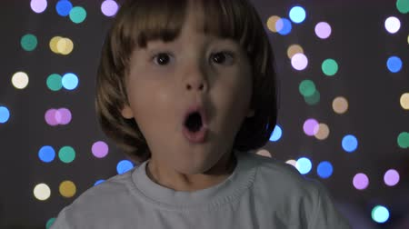 удивительный : Boy Looks Surprised and Happy to Receive Surprise. Portrait Little Boy Opening Eyes and Looking at Camera. Christmas New Year Background. Child Looks Into Camera With Delight and Surprise at Face. Стоковые видеозаписи