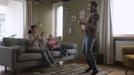 livingroom : Family Funny Leisure Activity. Happy Parents and Cute Funny Kids Dancing Laughing in Living Room. Mom And Dad With Little Children Having Fun together. Love Lifestyle Home. Slow Motion.