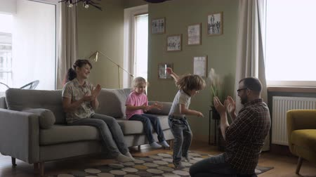 domy : Family Funny Leisure Activity. Happy Parents and Cute Funny Kids Dancing Laughing in Living Room. Mom And Dad With Little Children Having Fun together. Love Lifestyle Home. Slow Motion.
