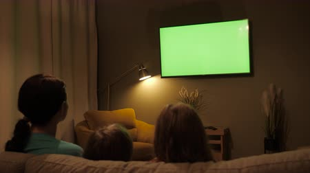 family watching tv : Family Sitting Together Sofa In Their Living Room Night Watching TV Green Screen. Rear View Of Family With Children Sitting On Sofa In Living Room Evening Watching Green Mock-up Screen TV Together. Stock Footage