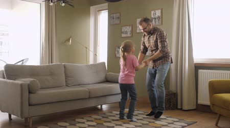 candid laughter : Young Father and Her Daughter Playing in Living Room. Funny Happy Family Father and Daughter are Dancing hold hands and jump at Home. Love Lifestyle Home. Slow Motion. Stock Footage