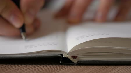 lista de verificação : A man turns over the blank pages of the diary. Businessman makes notes in a notebook.