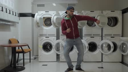 pense bête : Man Dancing Viral Dance And Have Fun In the Laundry Room. Happy Guy Enjoying Dance, Having Fun Together, Party. Joyful Man With beard in Cap and Glasses Dancing Cheerful In Laundry Room.