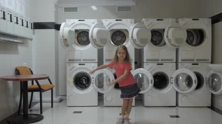 scuola di ballo : Happy Little Girl Dancing And Have Fun In Laundry Room. Child Enjoying Dance, Having Fun Together, Party. Floss Dance Viral, Flossing. Happy child portrait. Slow Motion. Filmati Stock