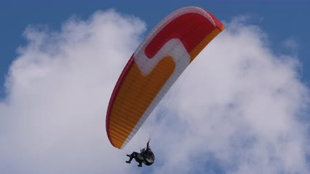 скольжение : Two People Flying Paraglider. Extreme Paraglider Flying Against Clear Blue Sky. Paragliding Tandem. Extreme Sport. Стоковые видеозаписи