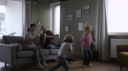 candid laughter : Family Funny Leisure Activity. Happy Parents and Cute Funny Kids Dancing Laughing in Living Room. Mom And Dad With Little Children Having Fun together. Love Lifestyle Home. Slow Motion.