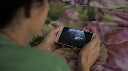 ginecologia : Pregnant Woman Looking at Ultrasound Scan on Smartphone Lying on Bed at Home. Third trimester pregnancy. Pregnant Woman Looking Ultrasound Video Her Baby on Mobile Phone. Gynecology Birth Childbirth.