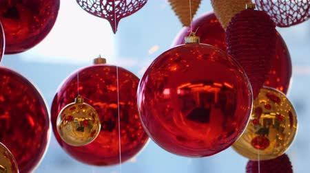hang : Christmas and New Year Decoration. Christmas Big Red Balls on Background of Luminous Lanterns and Gold Garlands. Holiday Background. Blinking Garland Red baubles With Lights Twinkling Close up.