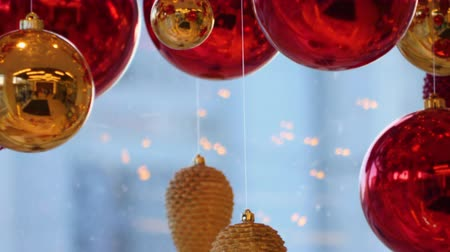 шишка : Christmas and New Year Decoration. Christmas Big Red Balls on Background of Luminous Lanterns and Gold Garlands. Holiday Background. Blinking Garland Red baubles With Lights Twinkling Close up.