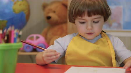 crayon couleurs : Four Year Old Caucasian Boy Having Fun Paints Picture On Paper, Being Creative and Artistic. Close Up Portrait Child Draws With Colored Pencil on Paper. Cute Little Child Boy is Sitting and Painting.
