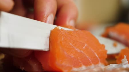 prepare food : Healthy Eating Sea Food Omega. Man Cutting Red Fish Salmon On Wooden Board Close Up. Chef Cuts Redfish, Most Delicious Meat Slow Motion. Macro Chef Cuts Salmon Fillet Slices For Cooking Sushi Closeup.