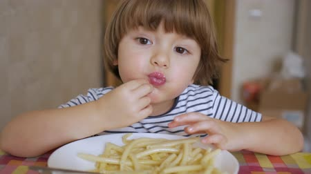makaróni : Cute Little Boy Eating Spaghetti With Cheese On Kitchen. Portrait Funny Healthy Preschool Kid Boy Eats Pasta Noodles. Hungry Child Eating With Hands And Smiling Healthy Food at Home. Stock mozgókép