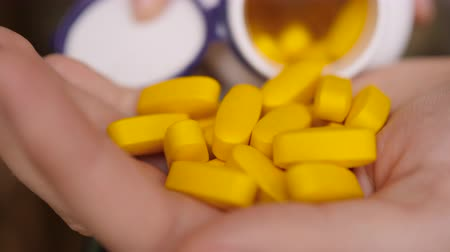 infarct : Vitamins And Supplements. Close up Hand Holding Variety of Yellow Pills on Palm. Slow motion. Medication Tablets, Capsules From Hand. Antidepressant, Headache, Soporific, Antibiotic Heart Attack.