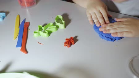 пластилин : Hands Child in Process of Modeling of Plasticine at Table in Nursery Room. Child Kid Boy Playing Colorful Clay Toy at Playroom of Home.