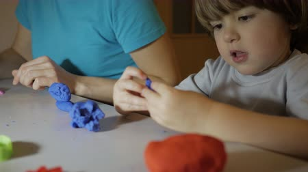 молдинг : Child in Process of Modeling of Plasticine at Table in Nursery Room. Child Kid Boy and Mother Playing Colorful Clay Toy at Playroom of Home. Young Woman and Son Playing With Colorful Clay in Nursery. Стоковые видеозаписи