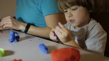 пластилин : Child in Process of Modeling of Plasticine at Table in Nursery Room. Child Kid Boy and Mother Playing Colorful Clay Toy at Playroom of Home. Young Woman and Son Playing With Colorful Clay in Nursery. Стоковые видеозаписи
