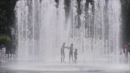 refrescar : Unrecognizable Silhouettes, Kids Having Fun Between Water Splash in Fountain on Street. Heat in Europe. Silhouettes Children Play in City Fountain on Hot Summer Day. Slow Motion. Global warming.