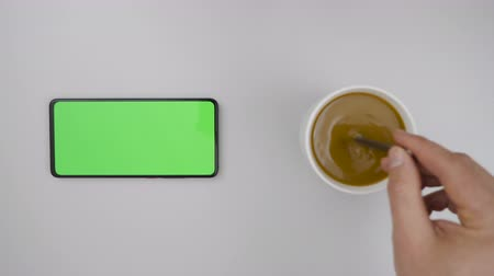 mock : Man Hand Cup of Hot Coffee and Using Smartphone Watching Green Screen Top View. Smartphone with Green Mock-up Screen Business Concept. Person Hand Stirring Coffee with Spoon on Table. Slow Motion.