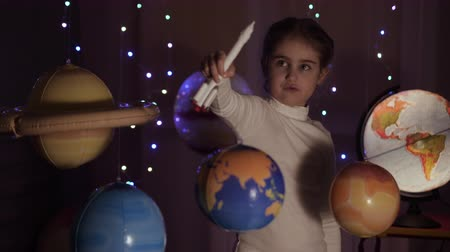 Space Travel Game Inspiration Spaceship. Little Kid Girl Astronaut Launching Toy Rocket From Spaceport Through Planets. Child Dreamer Playing With Toy Space Rocket Flying Among Planets. SLOW MOTION.