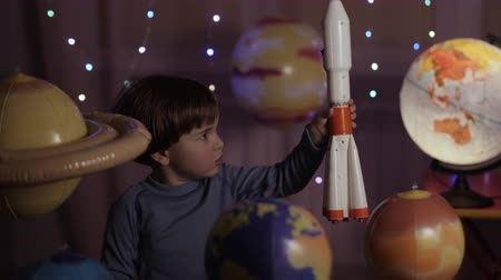 esploratore : Space Travel Gioco Ispirazione Astronave. Astronauta del ragazzo del bambino che lancia Toy Rocket From Spaceport attraverso i pianeti. Sognatore del bambino che gioca con Toy Space Rocket Flying Among Planets. RALLENTATORE.