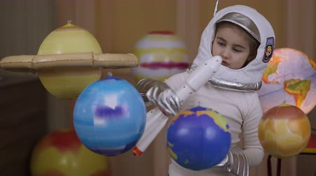 astronauta : Space Travel Game Inspiration Spaceship. Little Kid Girl Astronaut Launching Toy Rocket From Spaceport Through Planets. Child Dreamer Playing With Toy Space Rocket Flying Among Planets. SLOW MOTION.