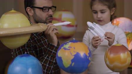 Space Travel Inspiration Spaceship. Little kid Girl Astronaut and Her Fther Launching Toy Rocket From Spaceport Through Planets. Daughter and Dad Dreamers Playing Toy Space Rocket Flying Among Planets Dostupné videozáznamy