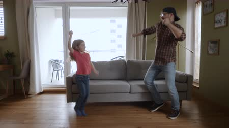 Happy Father and Daughter Dancing at Home Living Room, Fun Celebrating Funny Viral Dance Freedom Weekend. Family Enjoying Dance, Having Fun Party. Joyful Dad Daughter Dancing Cheerful In Living Room. Dostupné videozáznamy