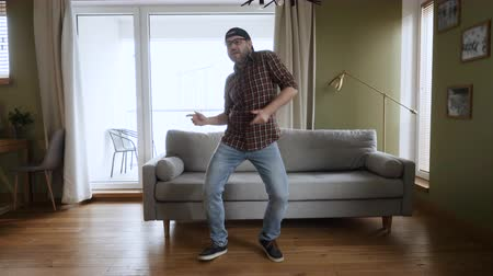 Happy Young Man Dancing at Home Living Room, Fun Celebrating Funny Viral Dance Freedom Weekend. Guy Enjoying Dance, Having Fun Party. Joyful Man Dancing Cheerful In Living Room. Slow Motion.