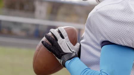 stanovena : American football. Determined American football player holding a ball with both his hands in slow motion. Close-up of american football player holding a ball. Preparing for the game. Training.