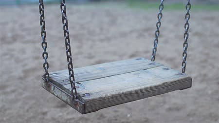 black dirt : Chain swing without children and child swinging empty in cloudy weather