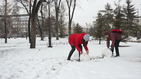 white cloths : a girl sculpts a snowman with her brother Stock Footage