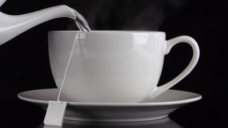 bolsa : Front view of hot water being poured from a teapot into a white cafe-style tea cup on a saucer against a black background with steam.