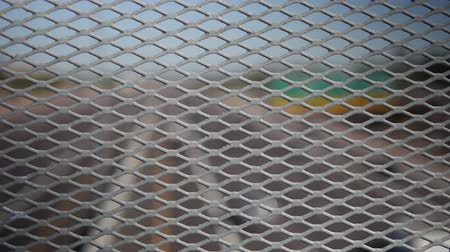 mesh : A close-up, straight-on view of a rusty, metal mesh overpass fence with a defocused desert highway scene with moderate traffic in the background. Recommended use: when you need a POV of a highway.