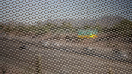 боке : A straight-on view of a rusty, metal mesh overpass fence with a defocused desert highway scene with moderate traffic in the background. Recommended use: when you need a POV of a highway.