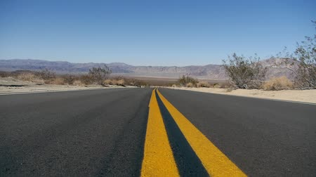 auto estrada : A left-to-right, low-to-ground Dolly-Shot on the center no-passing lanes of a long, desert road with desert, mountains, and blue sky stretching into the background.