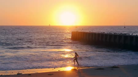 ancorado : A girl spins and plays in the beach waves at Playa Del Ray, Los Angeles, in an orange and yellow sunset on a blue ocean with anchored boats and a pier with standing flock of birds.
