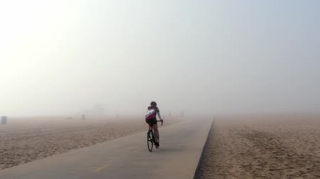 ciclismo : A woman rides a road bike on a bike path on the beach in Playa Del Ray, Los Angeles and then disappears in the fog.