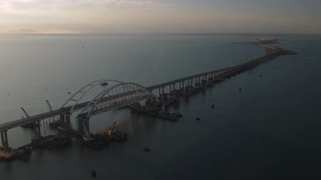 paving : KERCH, RUSSIA, May 16, 2018: Aerial view of The Crimean Bridge, Kerch Bridge, colloquially the Kerch Strait Bridge with road and rail passages across the Kerch Strait, which will connect the Taman Peninsula and the Crimea. Opening of the Crimean bridge 4k Stock Footage