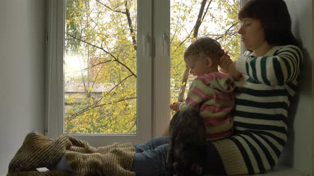 ceket : A young woman in a striped sweater. Girl stroking a cat. Good to sit on a warm windowill. Yellow leaves are falling outside.
