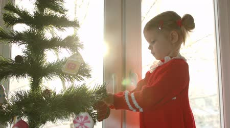 рождественская елка : Little girl in red dress decorating Christmas tree with some gingerbread in the form of a ball with blue snowflakes against the bright window, standing on the windowsill.