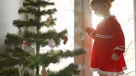 mézeskalács : Little girl in a red dress adorns ginger gingerbread snowman Christmas tree against the bright window, standing on the sill. Trees covered with snow, shining under the rays of the sun on the outdoor.