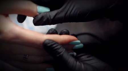 tampon : Nail technician in black gloves deals on fingers customer care cuticle oil close-up in bright light.