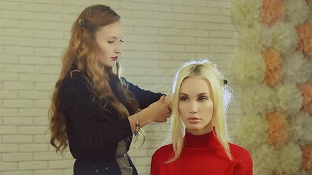 zvlněné : Hairdresser making curls on customer blond hair using electric curler in studio with white brick wall in background.