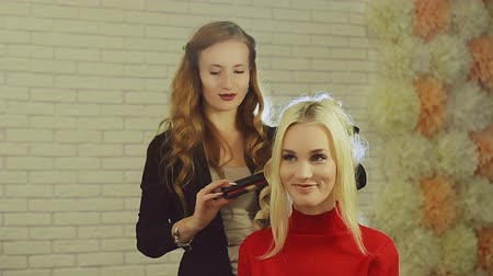 anelzinho : Hairdresser making curls on customer blond hair using electric curler in studio with white brick wall in background.